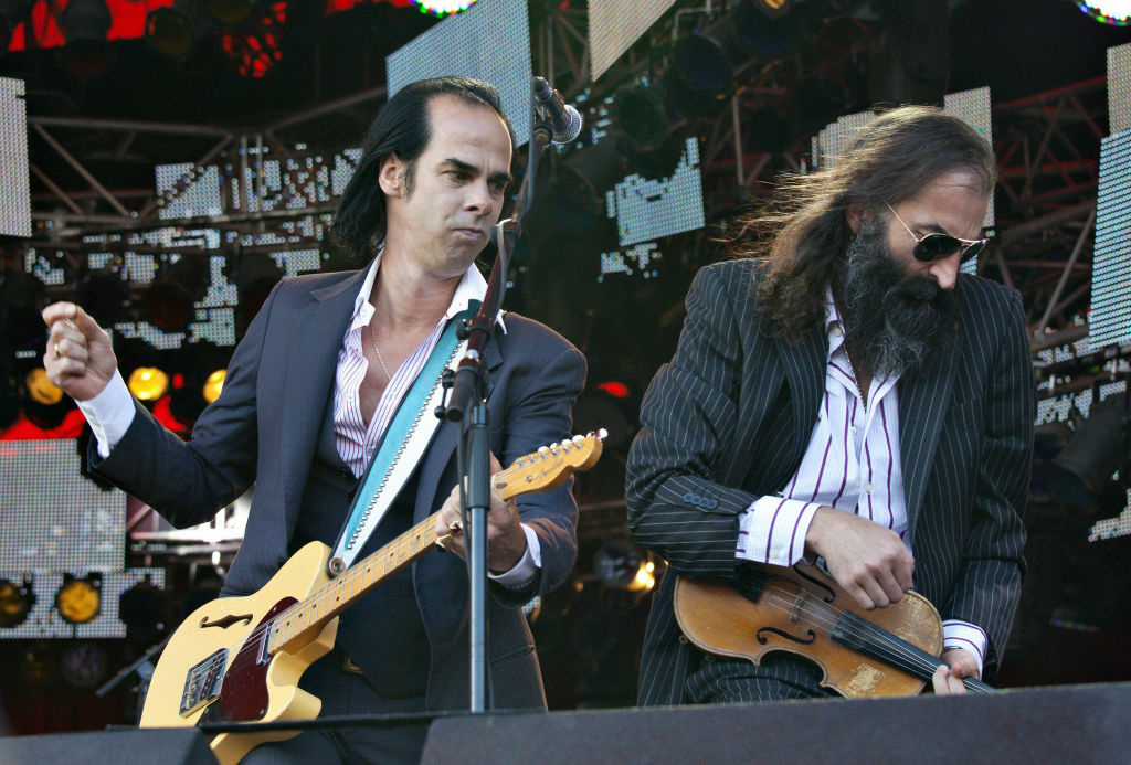 Australian singer Nick Cave (L) gestures during a performance with The Bad Seeds at the Roskilde festival in Roskilde on July 3, 2009.