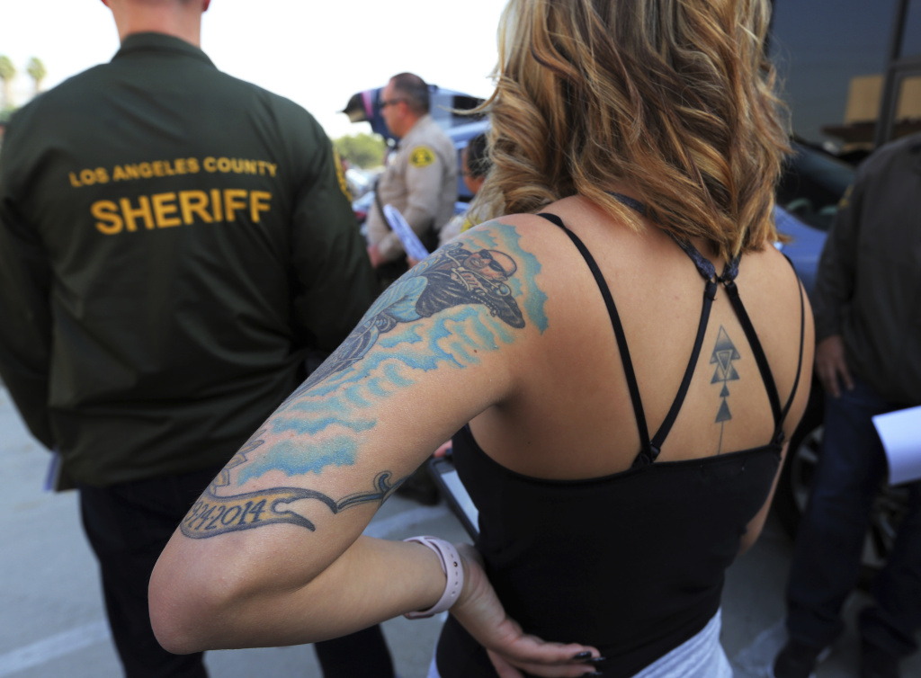 In this Wednesday, Nov. 15, 2017 photo, before an undercover sting operation, a sheriff's deputy who will pose as a prostitute listens at a briefing in Compton, Calif., a city some 15 miles south of Los Angeles. For hours, Los Angeles County sheriff's deputies listen to the same scenario play out over and over: men pull up alongside a woman pacing in front of an abandoned storefront in Compton and proposition her to have sex with him. They soon found themselves in handcuffs. The women were undercover Los Angeles County sheriff's deputies posing as prostitutes in a sting operation aimed at stemming the demand in the commercial sex industry.