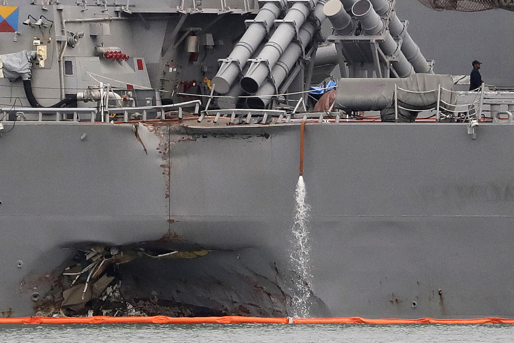 The damaged port aft hull of the USS John S. McCain, is visible while docked at Singapore's Changi naval base on Tuesday, Aug. 22, 2017 in Singapore. The focus of the search for U.S. sailors missing after a collision between the USS John S. McCain and an oil tanker in Southeast Asian waters shifted Tuesday to the damaged destroyer's flooded compartments. (AP Photo/Wong Maye-E)