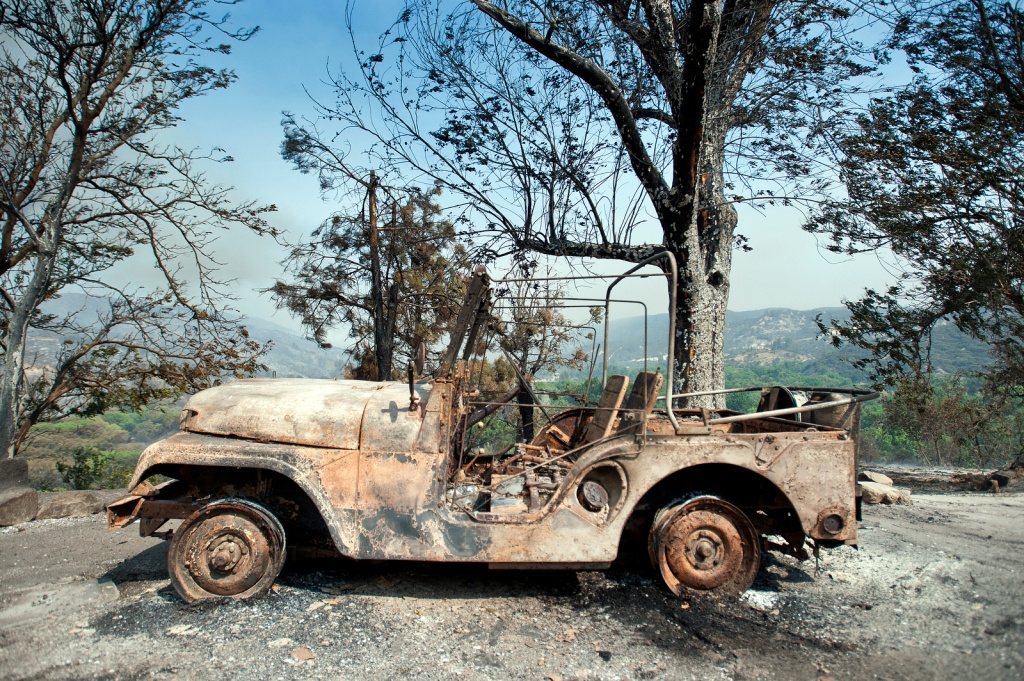 A scorched car is left in the driveway of a Lake Hughes home.