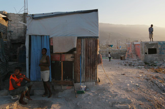 People around their home at approximately the time one year ago a massive earthquake jolted the city on Jan. 12, 2011 in Port-au-Prince, Haiti.
