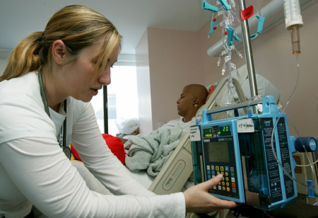 Registered nurse Autumn Small adjusts an IV drip machine for eighteen-year-old cancer patient Patrick McGill as he receives treatment for a rare form of cancer at the UCSF Comprehensive Cancer Center Childrens Hospital.