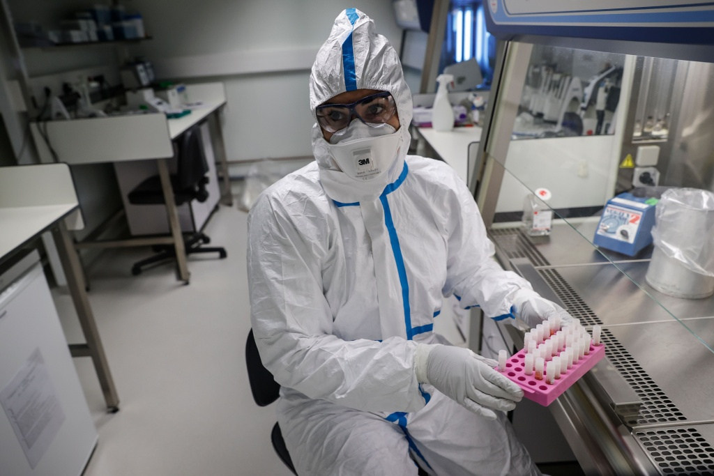 A laboratory operator wearing a protective gear handles patients' samples in a laboratory of the National Reference Center (CNR) for respiratory viruses at the Institut Pasteur in Paris on January 28, 2020.