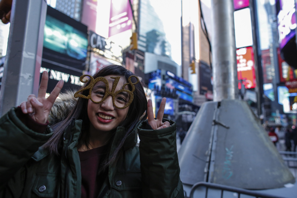 A woman poses in Times Square as she gets ready to attend the New Year's Eve celebration on December 31, 2017 in New York City.