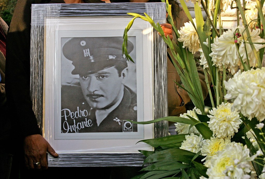 A fan holds a picture of the late Mexican actor and singer Pedro Infante, in front of his tomb during the commemoration of the 50th anniversary of his death at the cemetery The Garden, in Mexico City, 15 April, 2007. Known as the