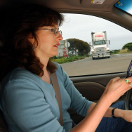 Catherine Singer dials a cell phone in her car as a truck approaches in San Clemente, California.