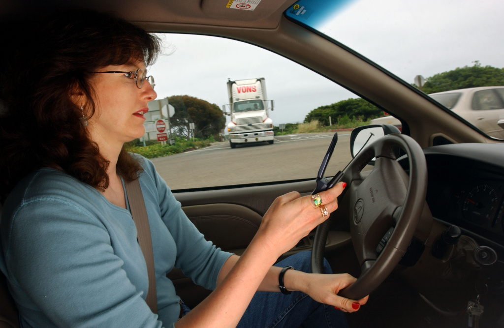 File: Catherine Singer dials a cell phone in her car as a truck approaches June 2, 2003 in San Clemente.