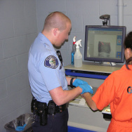 A U.S. Immigration and Customs Enforcement photo shows an individual being fingerprinted at a local jail facility under the Secure Communities program.