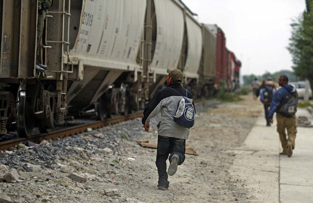 Salvadorean migrants run to jump on a train to the border with the United States, in Lecheria, 30 km north of Mexico City, on June 1, 2010.