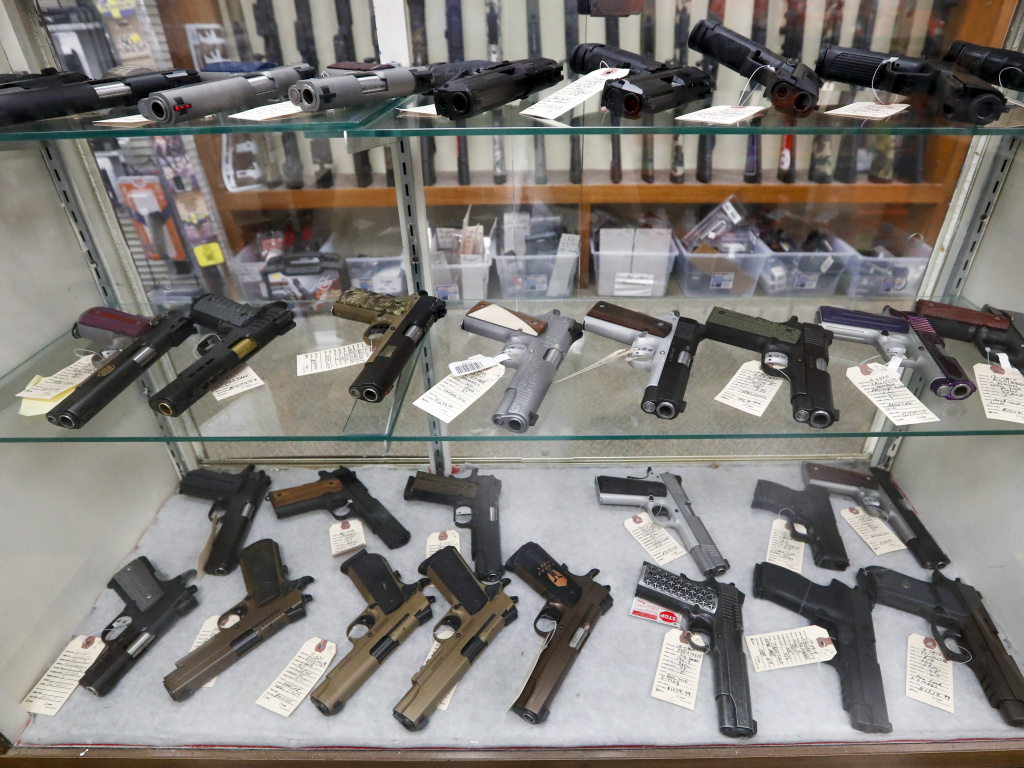 The FBI has reported a surge in background checks for gun sales. Here, firearms are for sale at a shop in New Castle, Pa.
