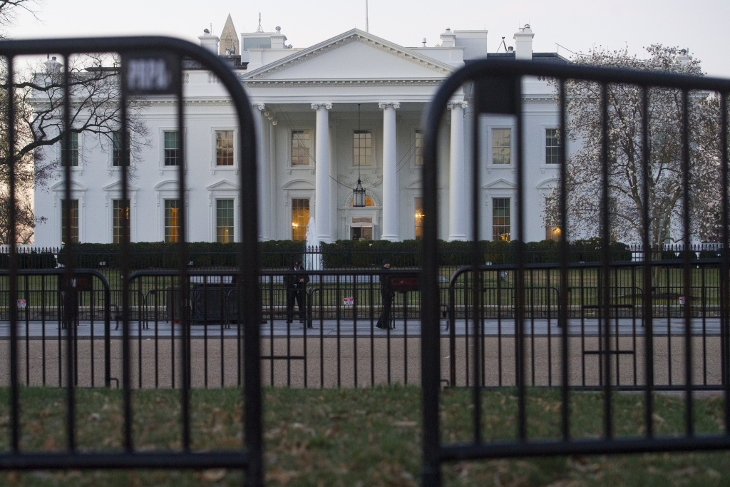In this March 24, 2019 photo, The White House is seen behind security barriers in Washington. A White House official turned whistleblower says dozens of people in President Donald Trump's administration were granted access to classified information despite