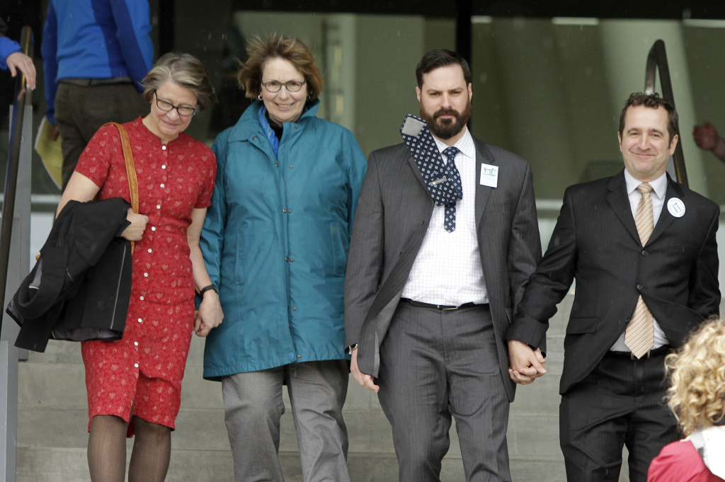 Plaintiffs, from left, Lisa Chickadonz, Christine Tanner, Ben West and Paul Rummell walk hand-in-hand out of federal court where a federal judge heard oral arguments in two cases challenging Oregon's ban on same-sex marriage in Eugene, Ore., Wednesday, April 23, 2014. U.S. District Judge Michael McShane threw out the voter-approved ban Monday.