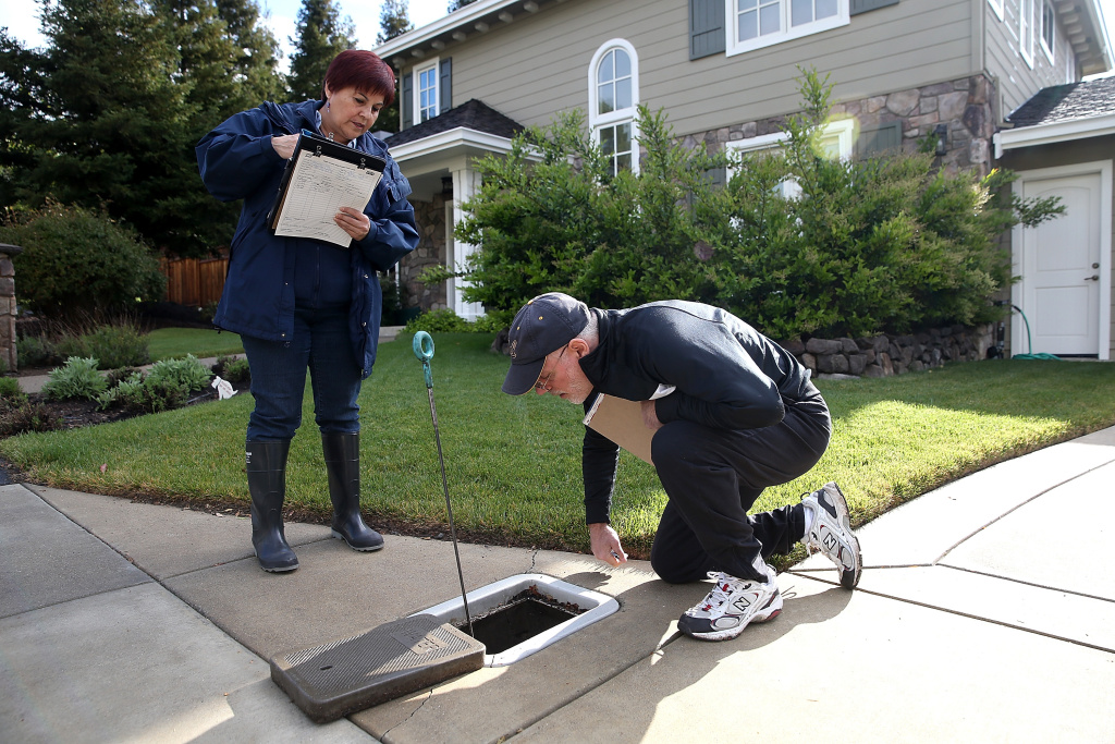 East Bay Municipal Utility District (EBMUD) water conservation technician Rachel Garza (L)  inspects a water meter with home owner Michael Shain as she performs a water conservation audit of a home on April 7, 2015 in Walnut Creek.