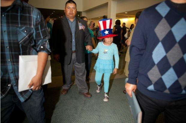 A newly naturalized U.S. citizen and his daughter - very much into the spirit of the occasion - leave a citizenship ceremony at the Los Angeles Convention Center, June 27, 2012.