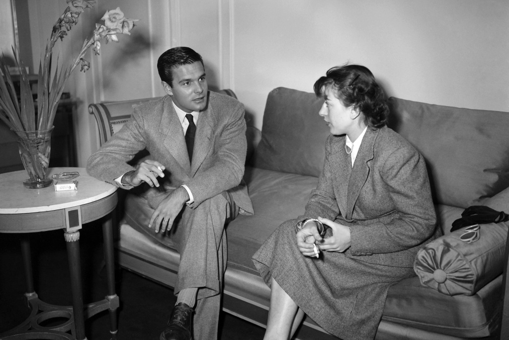 French actor Louis Jourdan (L) is seen discussing and smoking a cigarette with an unindentified friend during a party in Hollywood in June 1949. AFP PHOTO        (Photo credit should read -/AFP/Getty Images)