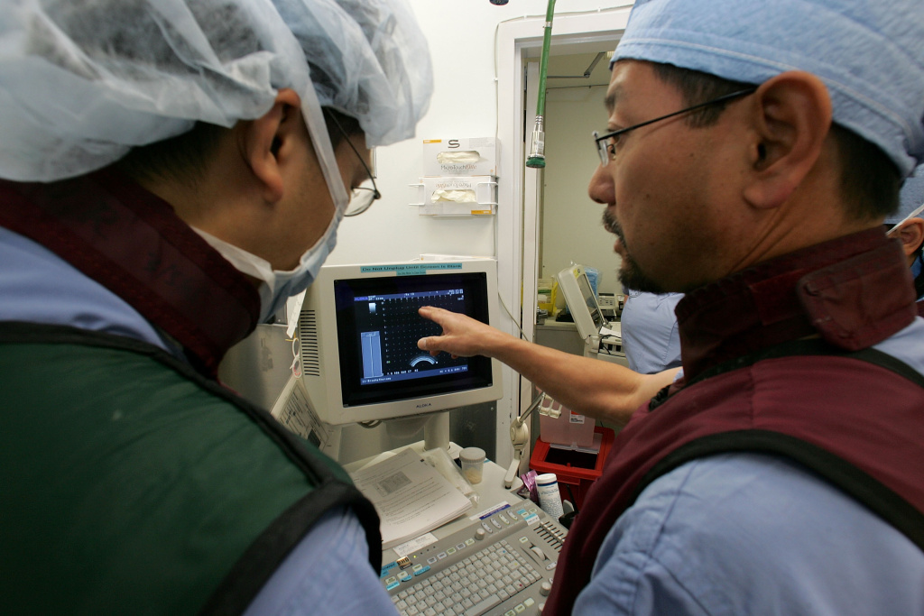 Dr. Katsuto Shinohara (R) and Dr. Surat Dhonsombat look at a video monitor as they perform a bracytherapy operation on a man with prostate cancer at the UCSF Comprehensive Cancer Center August 17, 2005 in San Francisco, California.