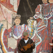 A man holds a violin near a mural at Mariachi Plaza during the annual procession and Mass in honor of the Feast Day of St. Cecilia, patron saint of music, Boyle Heights, 2008.