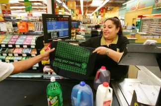 Food 4 Less grocery store general clerk Xochil Montenegro hands out a free reusable shopping bag, supplied by the California Grocers Association (CGA) and the City of Los Angeles, to a customer in observance of Earth Day, on the eve of Earth Day, April 21, 2008 in Los Angeles, California. During the two-day program, 50,000 bags are being handed out at about 40 grocery stores to encourage consumers to use reusable bags instead of disposable plastic or paper bags. The use of reusable bag has increased since a statewide plastic bag recycling law was enacted in July 2007 requiring grocers to provide in-store plastic bag recycling and to sell reusable shopping bags. Some communities have banned disposable plastic grocery bags. The free bags provided by the CGA and the city are made of 100% recycled water, soda and food containers.