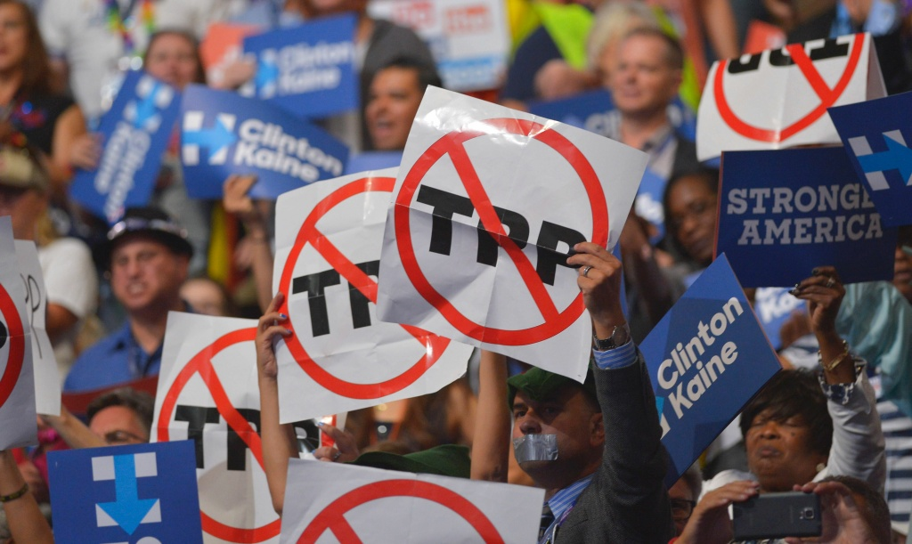 People hold signs against the Trans Pacific Partnership during the Democratic National Convention. The TPP has become a hot-button issue.