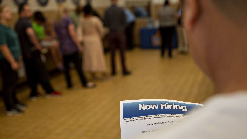 The U.S. has added jobs in every month for nearly eight years. Here, a job seeker holds an employment flier during a hiring event at an Aldi Supermarket in Darien, Ill., in July.