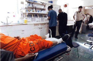 An inmate patient lies on a gurney in the Triage and Treatment Area (TTA), San Quentin's emergency room. The two bay treatment area in the Neumiller building serves the institution's more than 5,000 inmates.