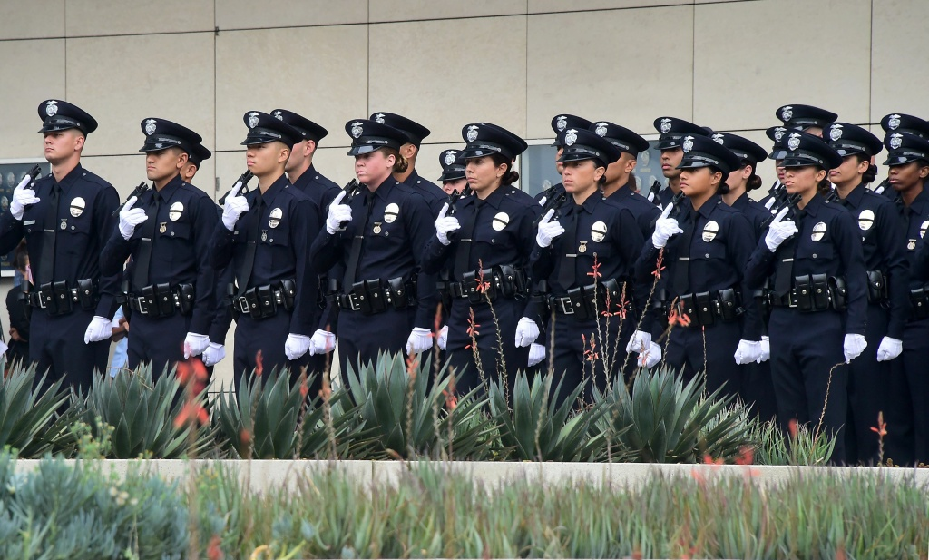 With black ribbons across their badge and holding a gun, police recruits attend their graduation ceremony at LAPD Headquarters where rappers Snoop Dogg and The Game led a peaceful demonstration outside on July 8, 2016 in Los Angeles, California, in what they called an effort to promote unity in the aftermath of the deadly shootings of police officers in Dallas.  / AFP / Frederic J. BROWN        (Photo credit should read FREDERIC J. BROWN/AFP/Getty Images)