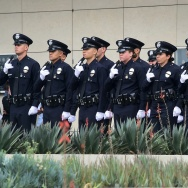 With black ribbons across their badge and holding a gun, police recruits attend their graduation ceremony at LAPD Headquarters.