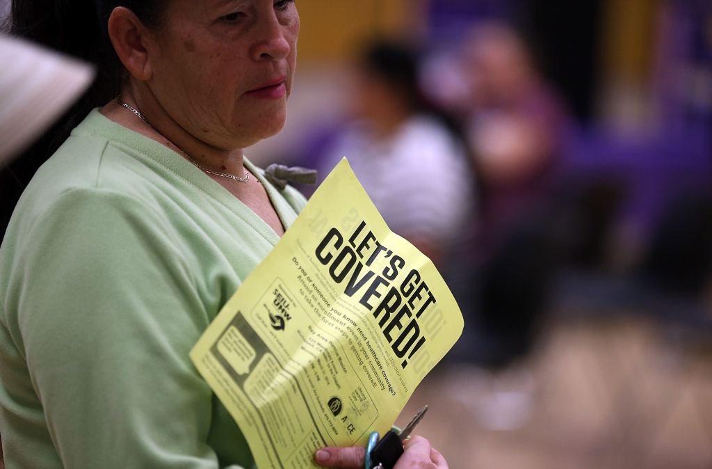 A woman holds a flyer as she waits to sign up for health insurance at a northern California enrollment fair in March.
