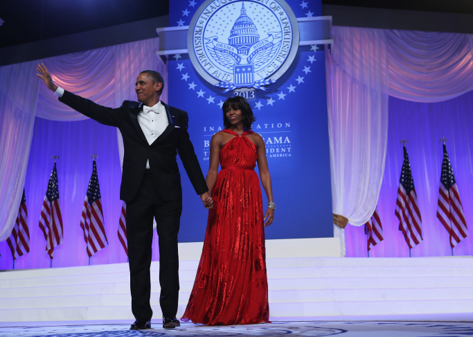 First lady Michelle Obama, in a silver Marchesa gown, and Comedian Joel Mchale share a laugh on stage at the annual White House Correspondent's Association Gala.
