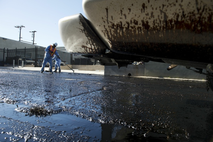 Crews clean up the remains of about 10,000 gallons of crude oil that sprayed into Los Angeles streets and onto buildings early Thursday morning, May 15 after a high-pressure pipe burst.