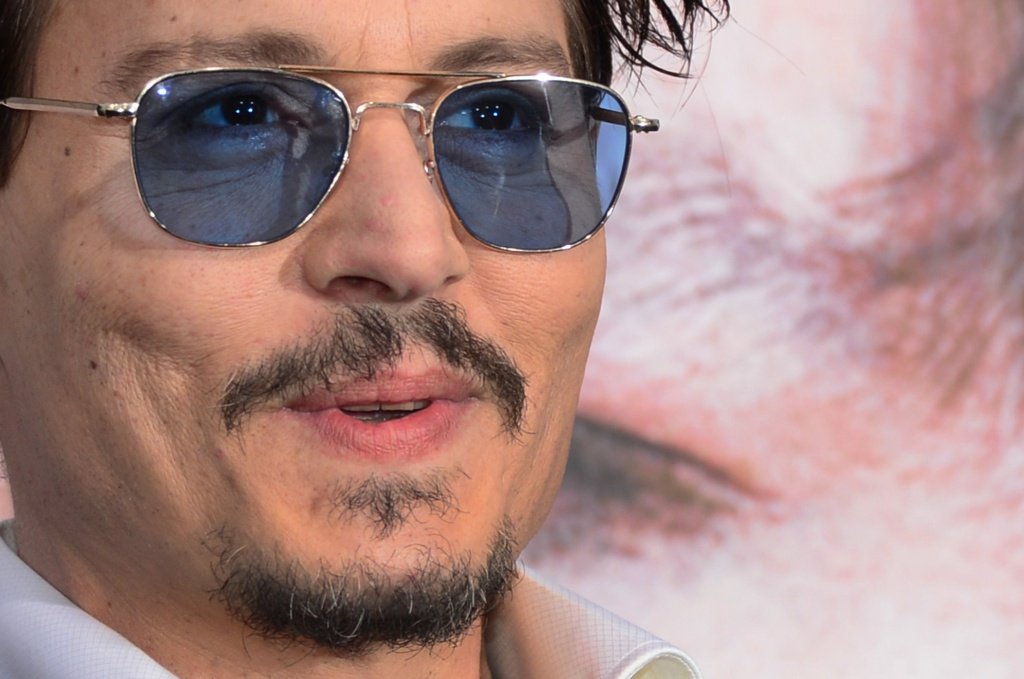 Actor Johnny Depp reacts to the photographers on arrival for the Los Angeles Premiere of the film 'Transcendence' on April 10, 2014 in Los Angeles, California.