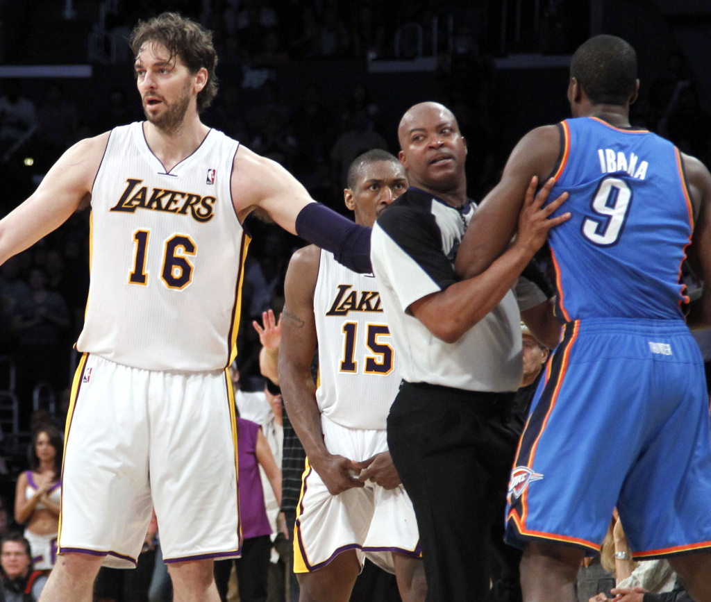 Los Angeles Lakers' Pau Gasol (16), of Spain, stands between an official and Oklahoma City Thunder player after Lakers' Metta World Peace (15) was called for a double flagrant foul and ejected from the game in the first half of an NBA basketball game on Sunday, April 22, 2012 in L.A.
