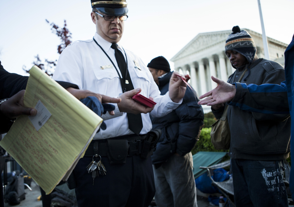 A police officer hands out tickets to view court arguments outside the US Supreme Court on March 26, 2012 in Washington, DC. The Supreme Court will hear arguments challenging the Constitutionality of the Obama Administration's health care reforms during the first of three days of arguments .