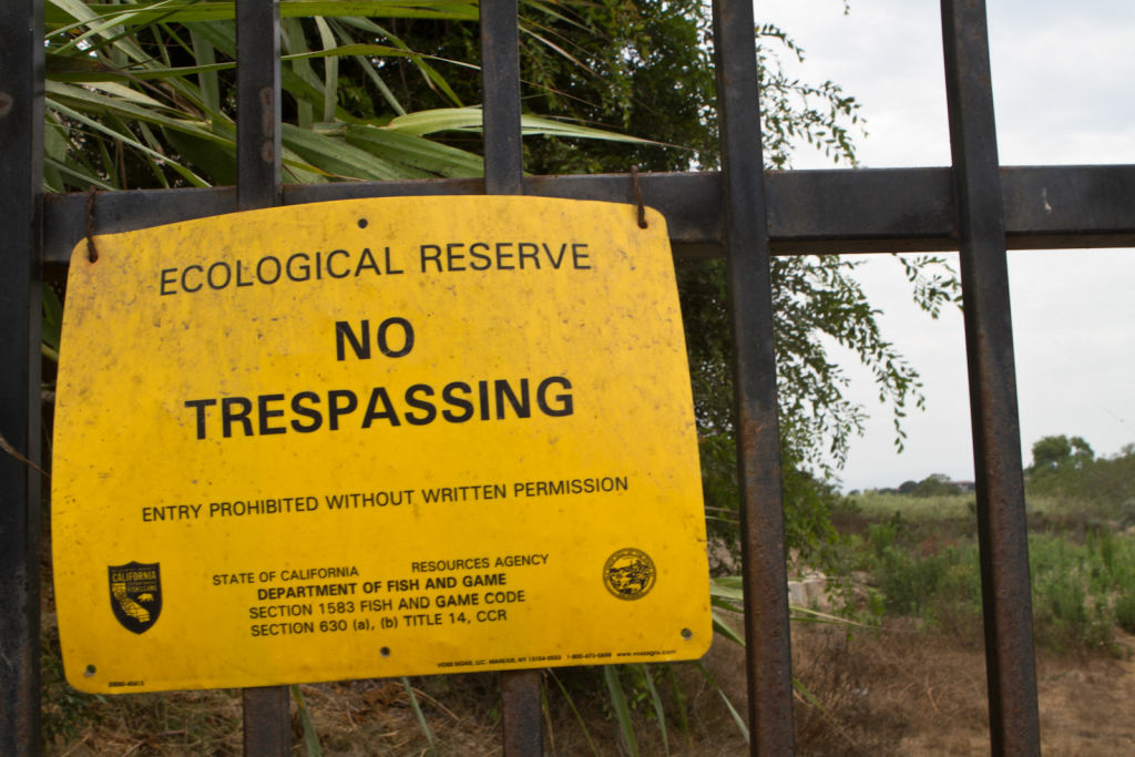 A sign posted on the locked fence warning people to not enter the Ballona Wetlands in Marina del Ray.