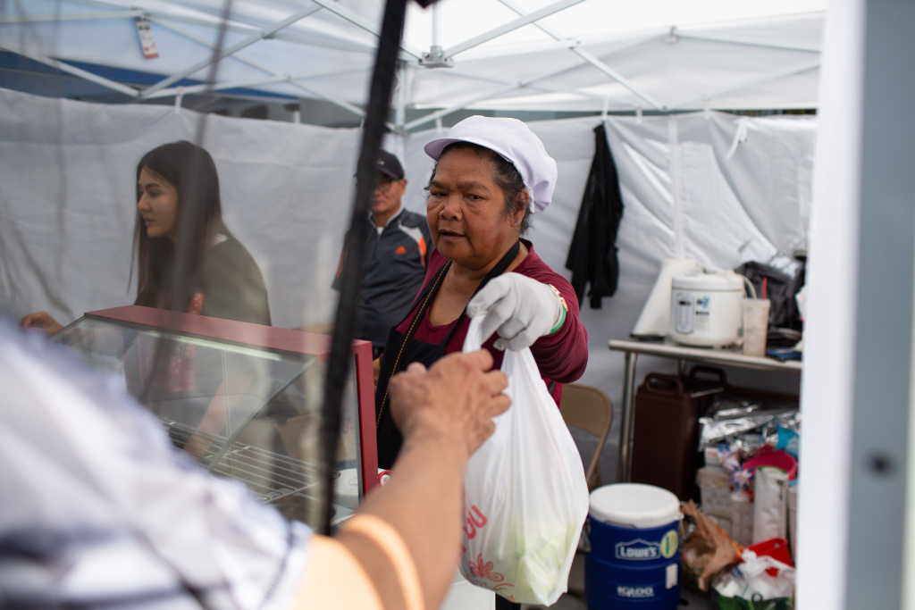 Customers buy Thai food from a stall at the East Hollywood Farmers Market, June 6, 2019. (James Bernal for KPCC)