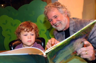 Grandson Miles reads with his grandfather, Chuck Leavell.
