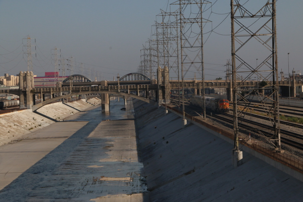 View of the Los Angeles River encased in concrete surrounded by railroad tracks and factories in downtown.