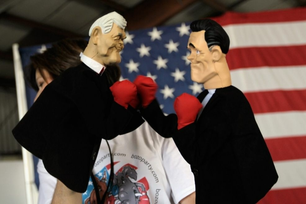 Lynn Coffin holds boxing hand puppets of former Speaker Newt Gingrich (left) and former Gov. Mitt Romney during a campaign event this week in Sarasota, Fla.