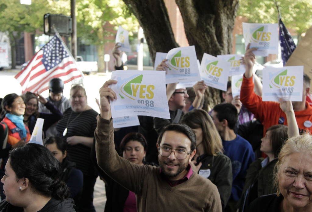 A crowd of Measure 88 supporters wave signs during a rally in Portland, Ore.  Measure 88 would require the Oregon Department of Transportation to issue driver cards to Oregon residents meeting specified eligibility, without requiring proof of legal presence in United States.