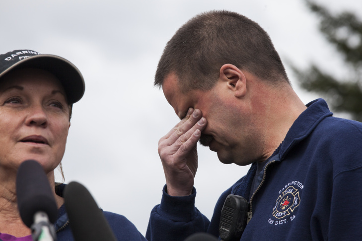 Darrington Fire District 24 volunteer firefighters Jan McClelland (L) and Eric Finzimer (R) speak to the media during an emotional press conference on March 26, 2014 in Darrington, Washington. The two were among the first to respond to the scene of a massive mudslide on March 22 in nearby Oso, Washington that authorities say killed at least 25 and left scores missing.