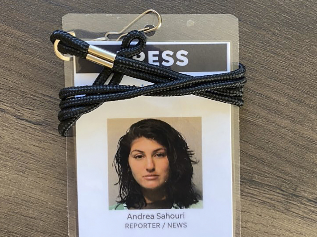A press badge for <em>Des Moines Register</em> reporter Andrea Sahouri features the jail booking photo from her May 31 arrest while covering a Black Lives Matter protest.