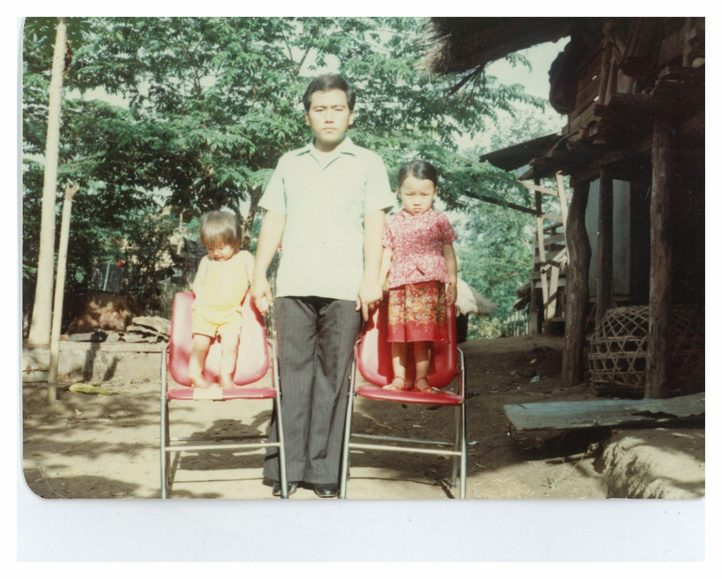 An image of author Kao Kalia Yang as a child, holding hands with her father, Bee.