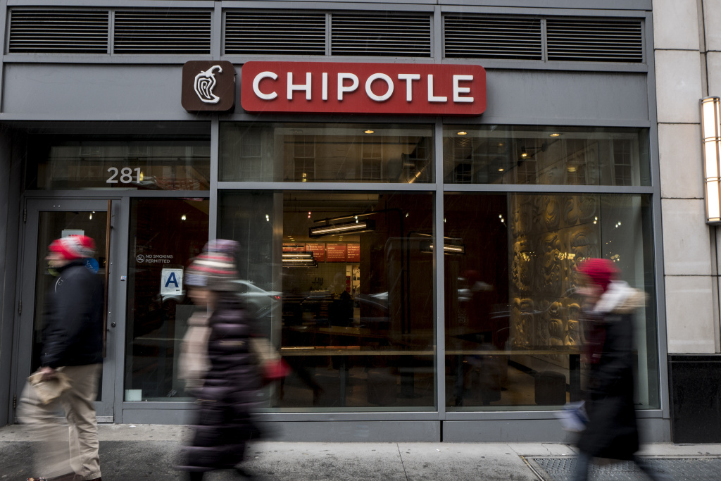 People walk past a Chipotle restaurant on Broadway in Lower Manhattan on February 8, 2016 in New York City.