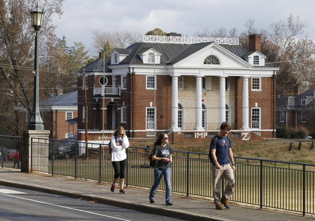 FILE - In this Monday, Nov. 24, 2014, file photo, University of Virginia students walk to campus past the Phi Kappa Psi fraternity house at the University of Virginia in Charlottesville, Va. Rolling Stone is casting doubt on the account it published of a young woman who says she was gang-raped at a Phi Kappa Psi fraternity party at the school, saying there now appear to be discrepancies in the student's account.