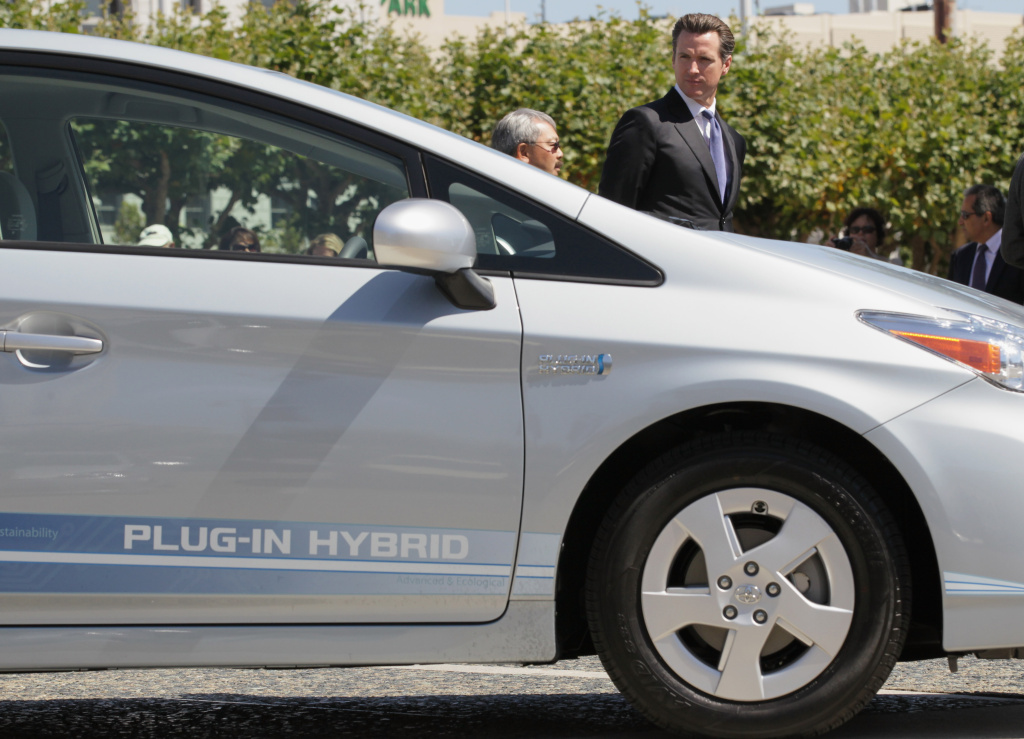 Gavin Newsom looks at a plug-in version of Toyota Prius in 2010 for a city evaluation in San Francisco.