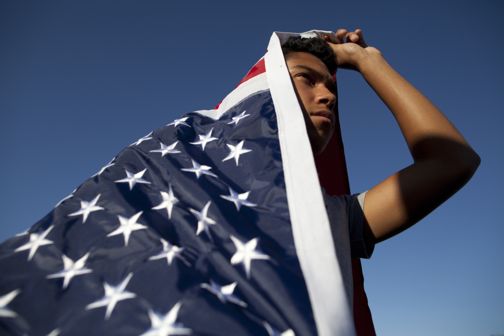 In this file photo, William Bello of Upland is draped in an American flag during a pro-immigration vigil in 2014 in Murrieta.