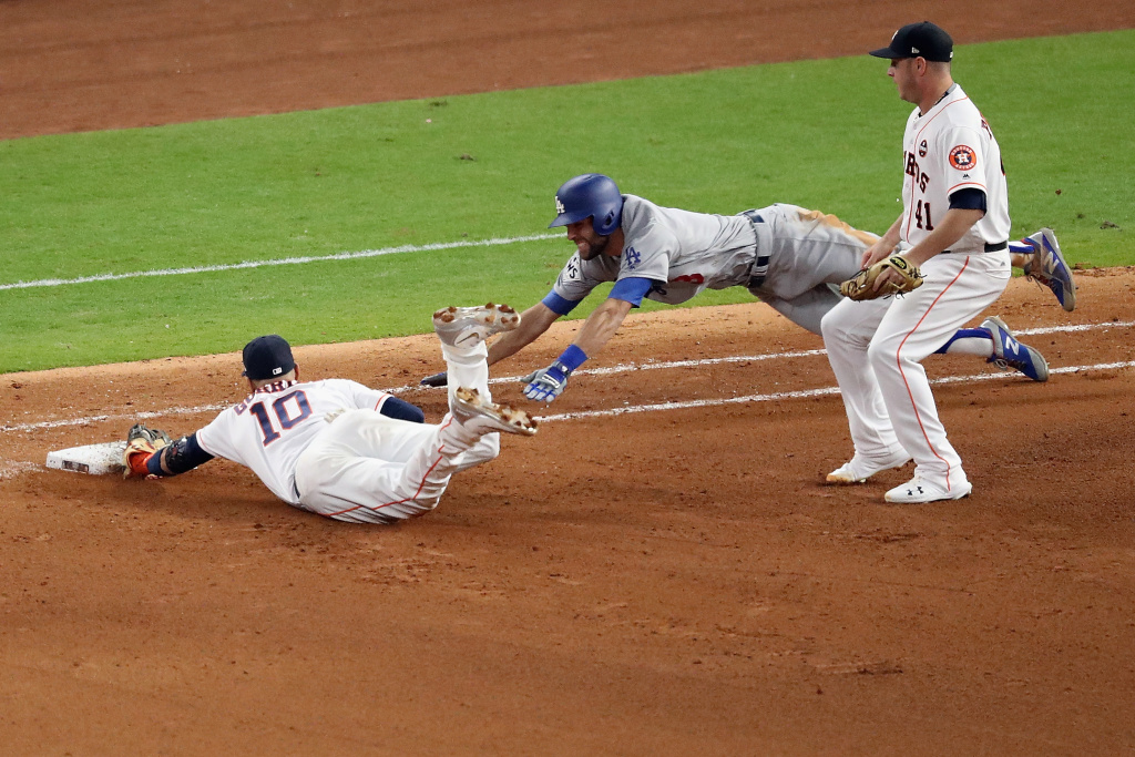 Yuli Gurriel (#10) of the Houston Astros dives to tag first base for the out as Chris Taylor (#3) of the Los Angeles Dodgers slides during the seventh inning in Game 3 of the 2017 World Series on October 27, 2017 in Houston, Texas.