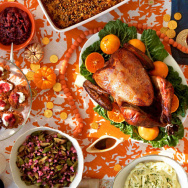 Manischewitz-brined turkey centers the Thanksgivukkah feast, surrounded by challah-apple stuffing, sweet potato bourbon noodle kugel, horseradish-spiked mashed potatoes, brussels sprouts with pastrami and pickled onions, and latkes with cranberry applesau