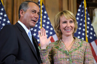 In this Jan. 5, 2011 file photo, House Speaker John Boehner reenacts the swearing in of Rep. Gabrielle Giffords, D-Ariz., on Capitol Hill in Washington.