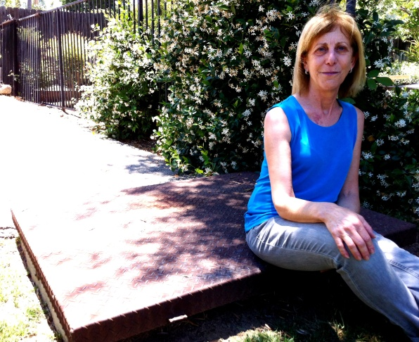 Deb Kaufman sits on the lid of the fallout shelter her dad, nuclear engineer Alvin B. Kaufman, built in their back yard in Woodland Hills.